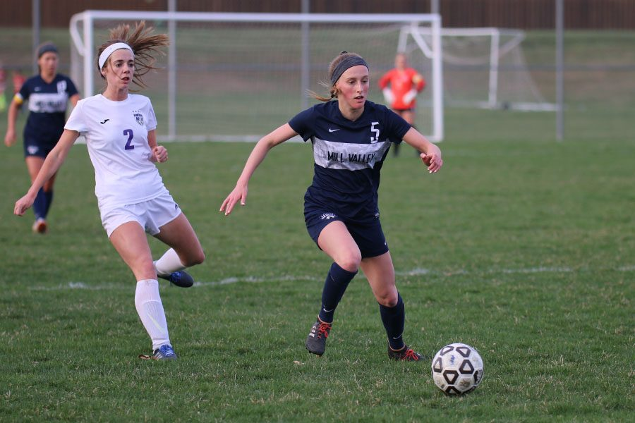 Racing toward the ball, junior Annie Hoog moves the ball away from the goal.