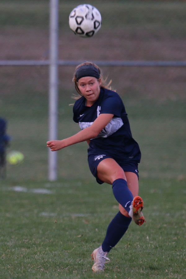Eyes locked down the field, senior Shyanne Best kicks the ball.