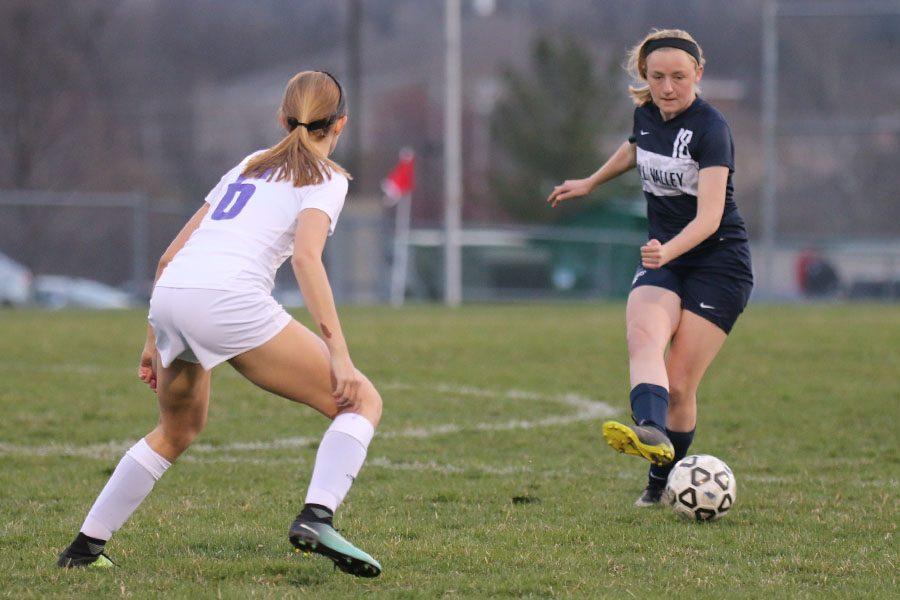 As a defender applies pressure, sophomore Anna Ricker kicks the ball to a teammate.