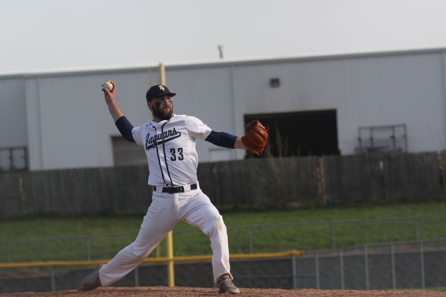 Extending+his+arm+backwards%2C+senior+Ethan+Keopke+throws+a+pitch+against+Bishop+Miege.+