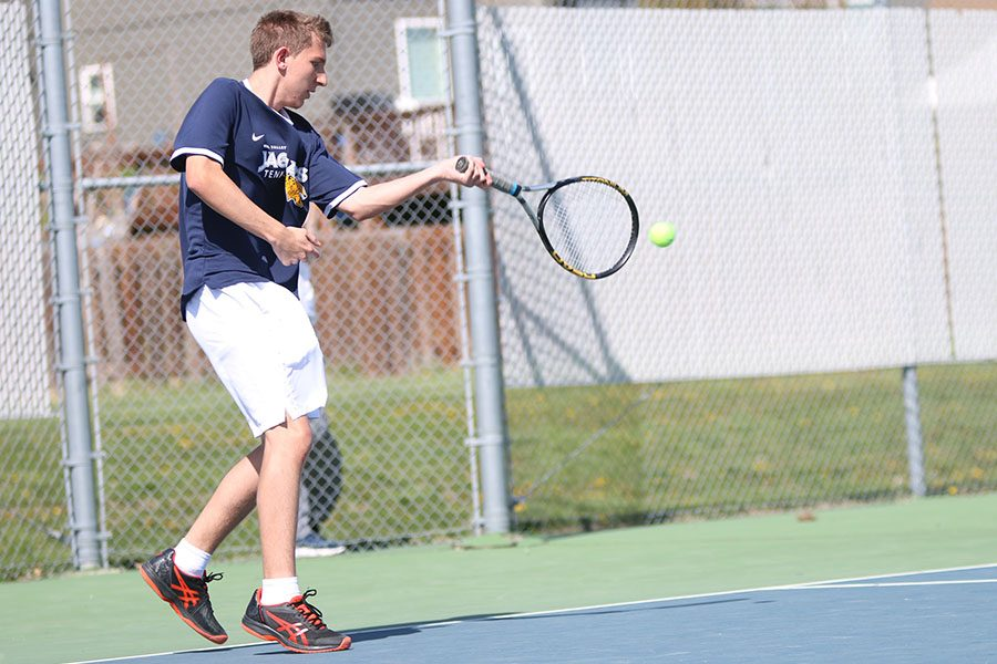 In his double match with senior Andrew Lewis, sophomore John Scarpa returns the ball off a serve.