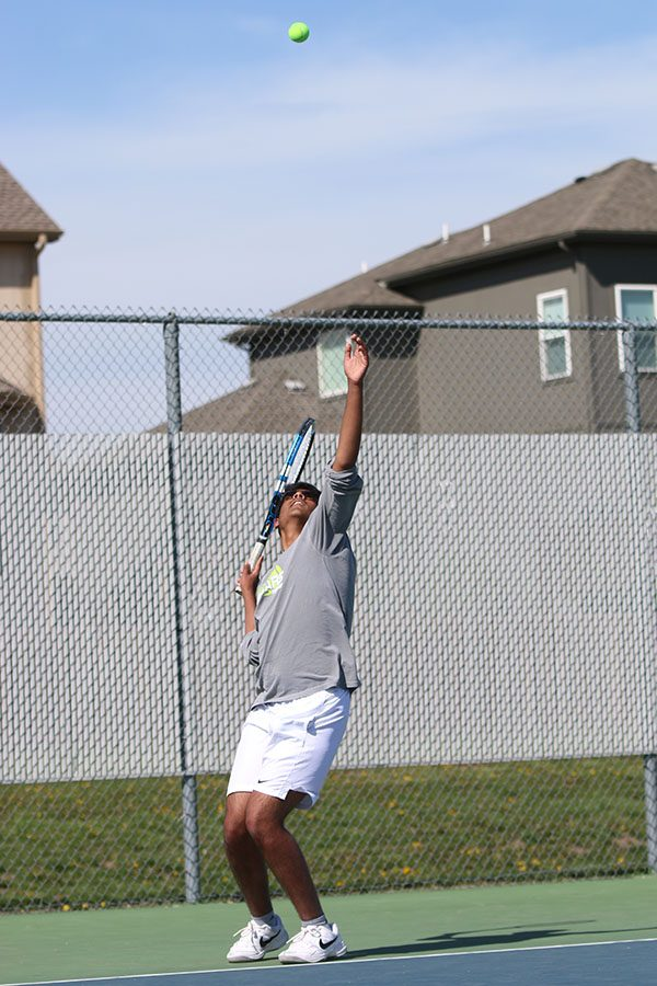 Beginning a new game, junior Srikar Turaga tosses up the ball for his serve.