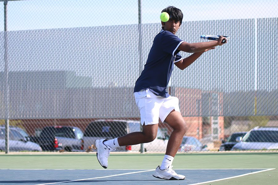 After a strong return from his opponent, junior Manoj Turaga winds up for a backhand.