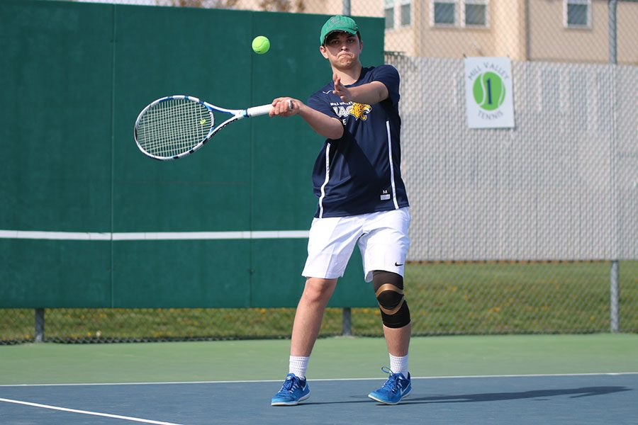 Setting his feet near the service line, senior Andrew Lewis hits a forehand return.
