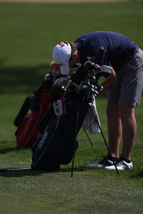 Looking through his bag, sophomore Nicklaus Mason pulls out his putter.