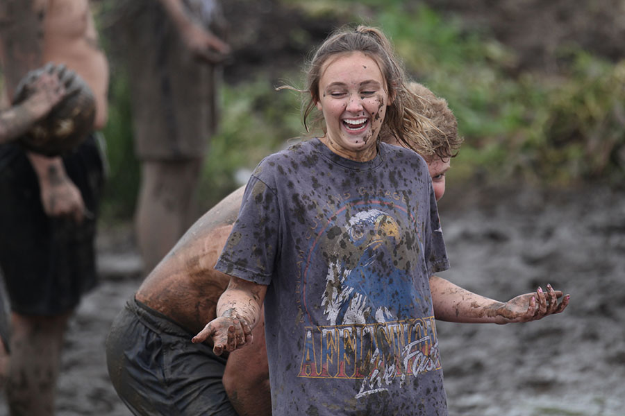 Junior+Audrey+Grabmeier+laughs+while+junior+Kyle+Kelly+hides+behind+her+to+avoid+being+splashed+with+mud.
