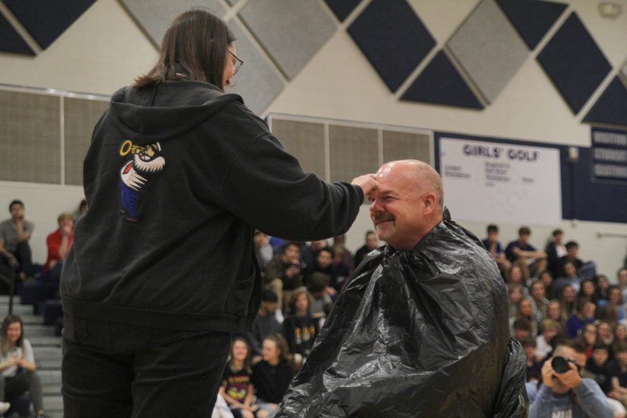 Preparing to pie principal Tobie Waldeck in the face, band director Deb Steiner paints whipped cream onto his forehead. Steiner received the honor after bringing in the most mobility devices for the Crutches for Africa drive, hosted by Youth for Refugees.