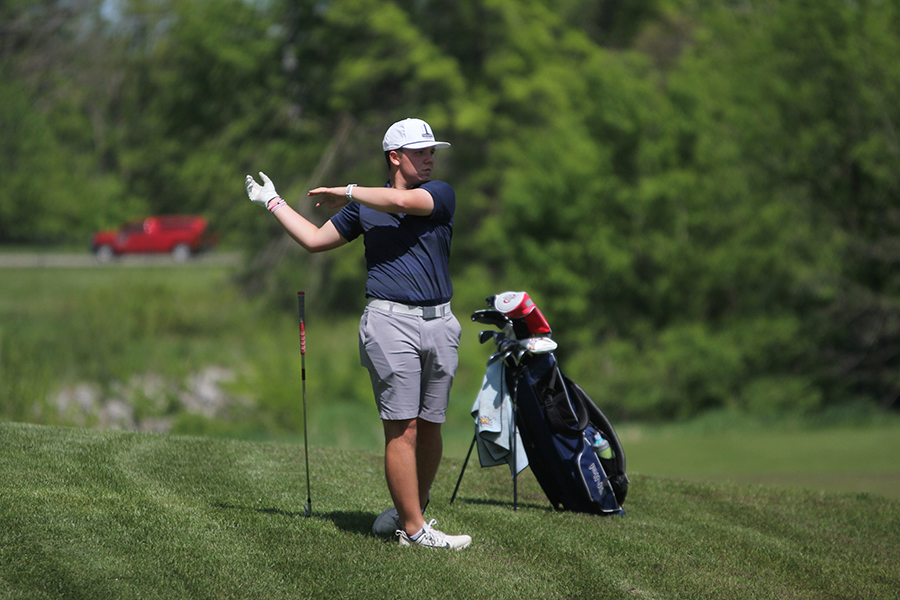 Along the green of hole 9, junior Charlie Flick watches  for where his shot will land.