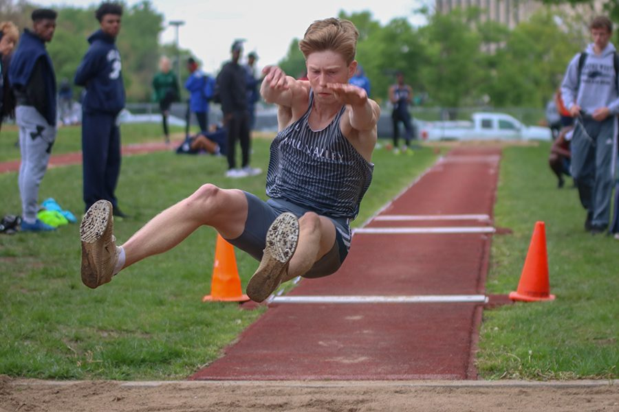 Stretching his limbs out to gain the more distance, senior Harry Arenholtz competes in the long jump.