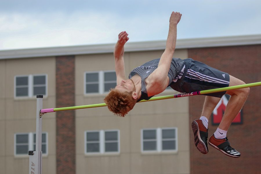 Throwing his arms in the air, junior Braedan Wiltse clears the bar.
