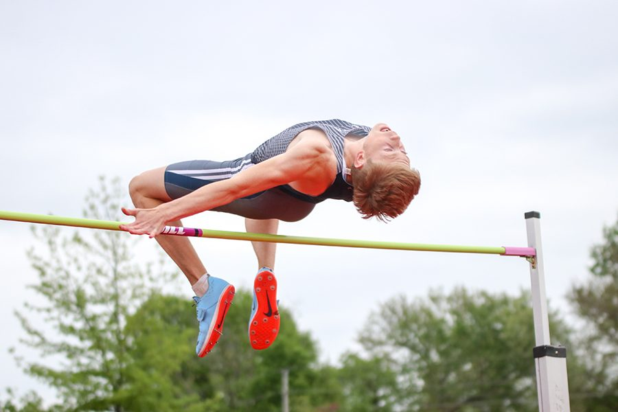 After jumping, senior Harry Arenholtz arches his back to clear the bar. Arenholtz finished second in the high jump.