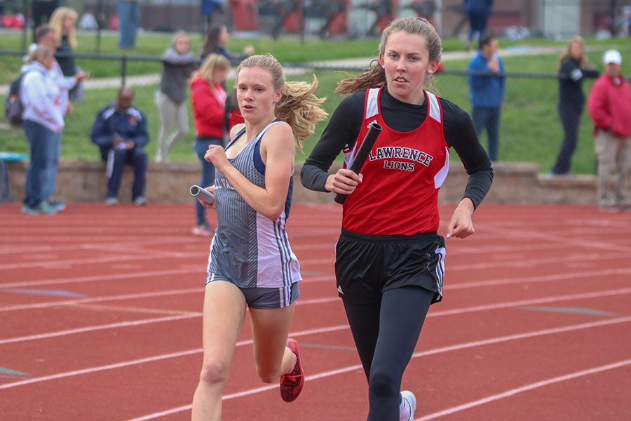 Coming around turn one, freshman Katie Schwartzkopf passes a Lawrence High School in the 4x800 meter relay. The relay team finished first.