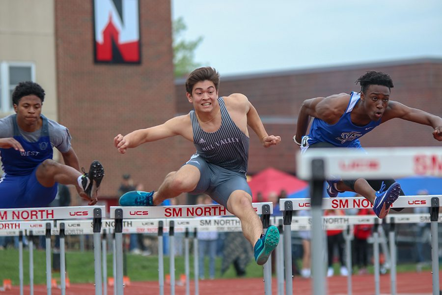 In the 110 meter hurdles, senior Eli Midyett tries to beat a Leavenworth sprinter.