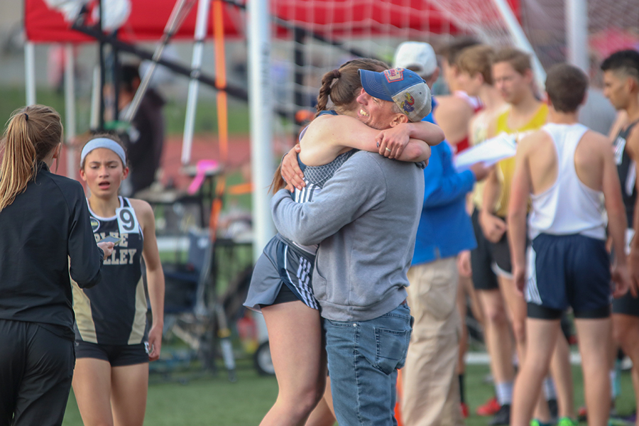 After+finishing+the+1600+meter+run%2C+senior+Delaney+Kemp+and+head+track+coach+Chris+McAfee+hug.+