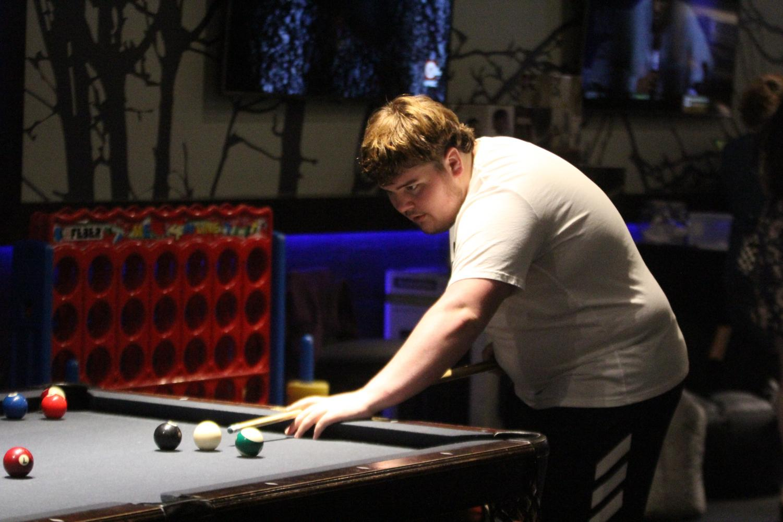 Focusing%2C+junior+Duncan+Haines+Mills+plays+a+game+of+pool.