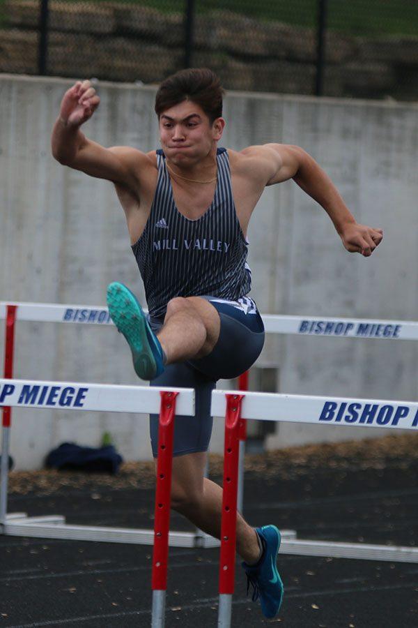 Preparing to jump over a hurdle, senior Eli Midyett competes 110m hurdles.
