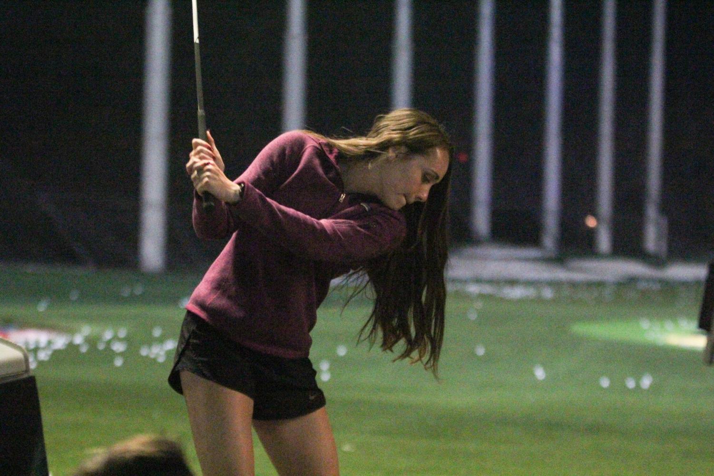 Holding+up+a+golf+club%2C+senior+Delaney+Kemp+prepares+to+hit+the+ball.
