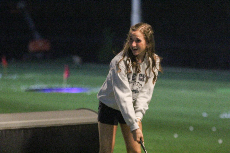 Holding+a+golf+club%2C+junior+Morgan+Koca+gets+ready+to+hit+the+golf+ball.