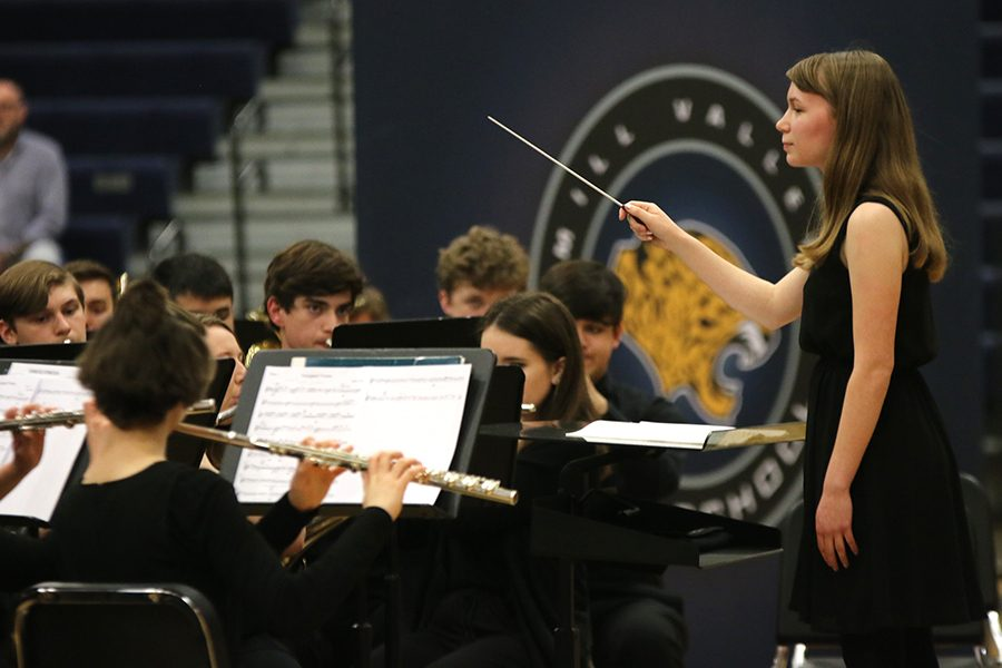 """Signaling a decrescendo in the music, senior Megan Dillon directs the band. Dillon composed the piece """"Variegated Visions"""" to showcase her journey through high school."""
