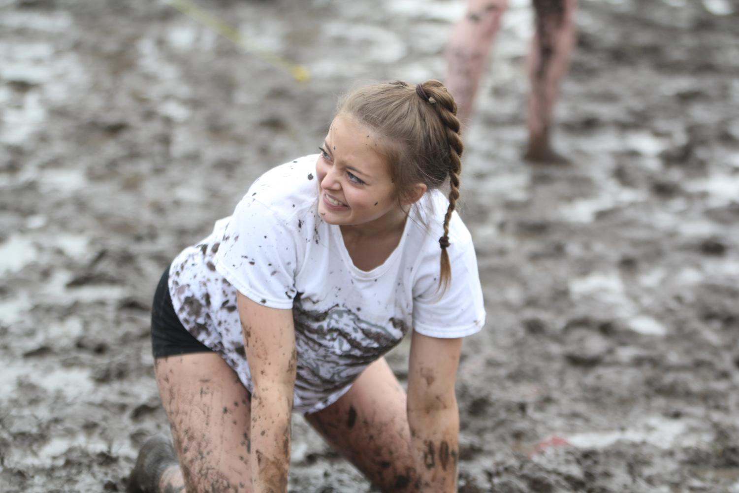 Laughing%2C+freshman+Paige+Totzke+gets+back+up+after+falling+in+the+mud.