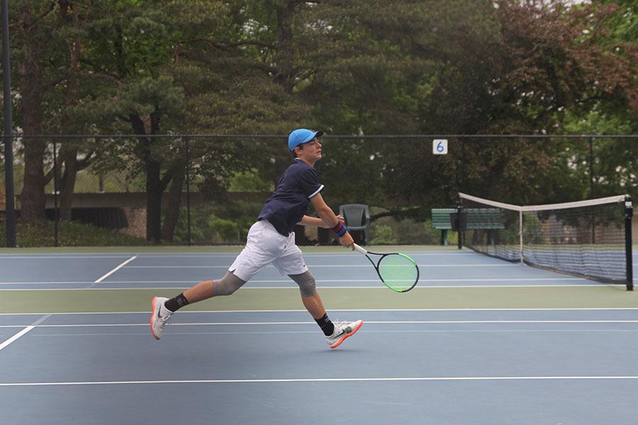 Bringing+down+his+racket%2C+freshman+Gage+Foltz+steps+towards+the+net.+%0A