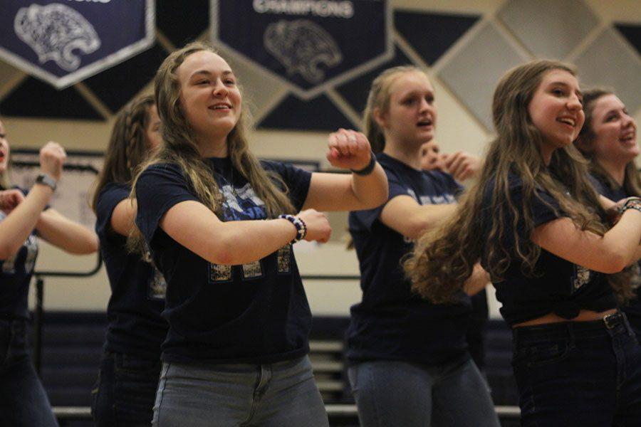 Smiling toward the crowd, junior Trinity Ouellette dances alongside members of the Grace Notes choir.