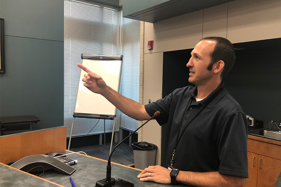 District technology director Brandon Riffel gestures as he lays out the new MacBook handbook.