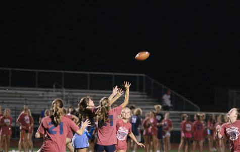 Multiple juniors try to stop senior girl from catching the ball.