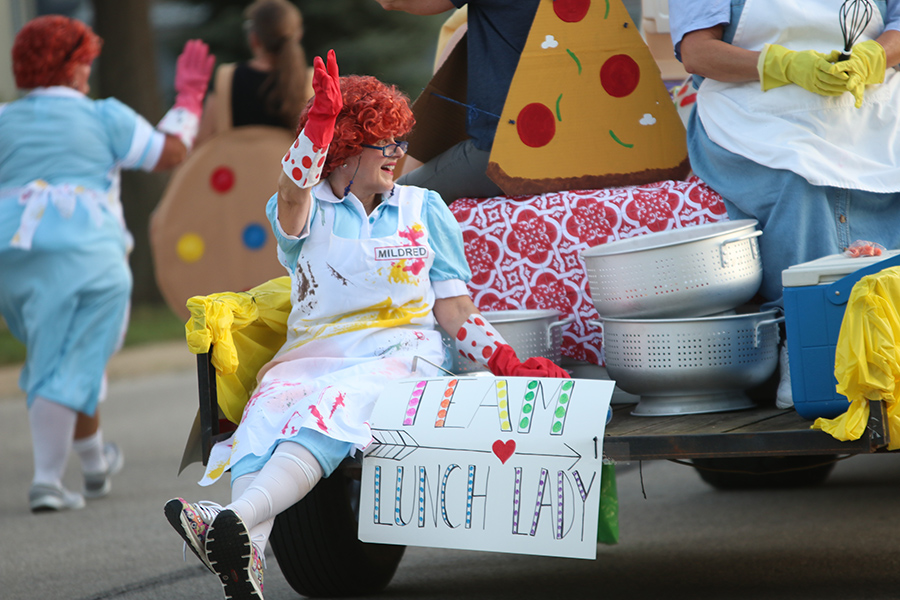 As the parade comes to a close, one of the lunch ladies waves to the public from the back of her float.