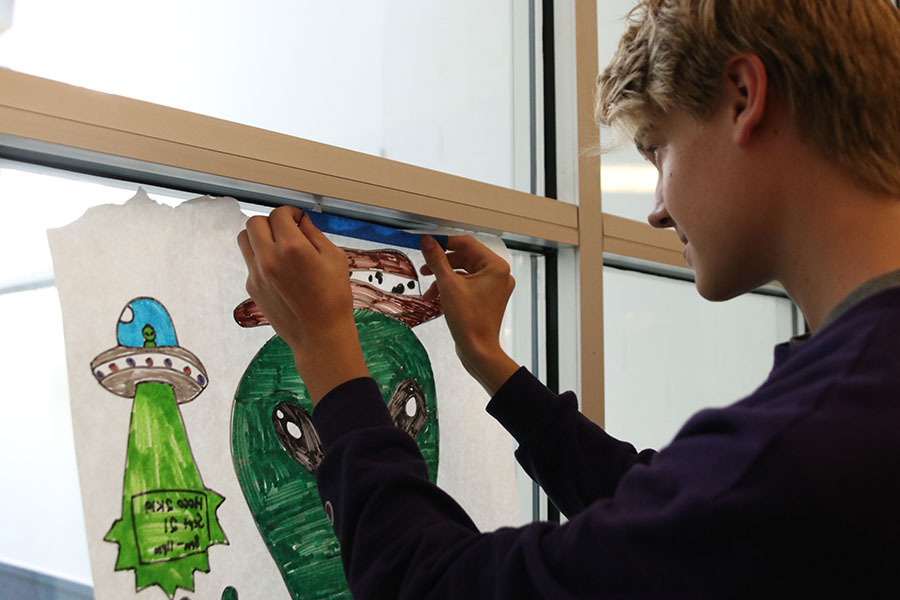 Sophomore Bret Weber hangs up homecoming posters for StuCo.