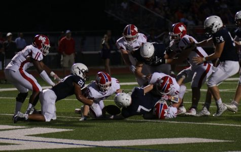 Junior quarterback Cooper Marsh extends his arm over the goal line for a touchdown, cutting the Jaguar deficit against Bishop Miege to seven points.