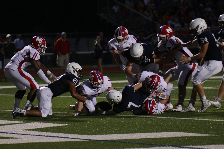 Junior quarterback Cooper Marsh extends his arm over the goal line for a touchdown, cutting the Jaguar deficit against Bishop Miege to seven points.