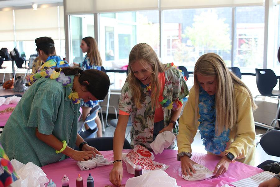 Sophomores Quincy Hubert, Katie Schwartzkopf and Bridget Roy prepare to tie-dye their T-shirts.