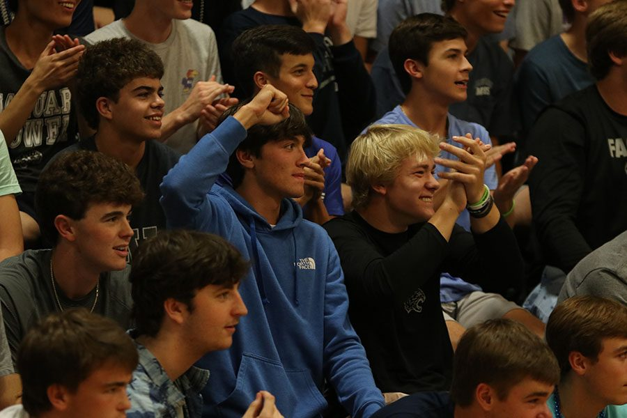 Cheering, seniors Anthony Pentola and Grant Frost watch as the homecoming candidates are introduced.