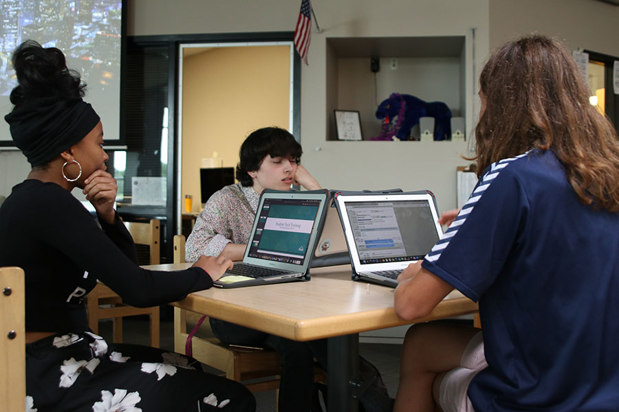 Working together in the library, seniors Aidan Thomas and Daniella Phale and junior Cameron Long check to see if any teachers need their assistance.