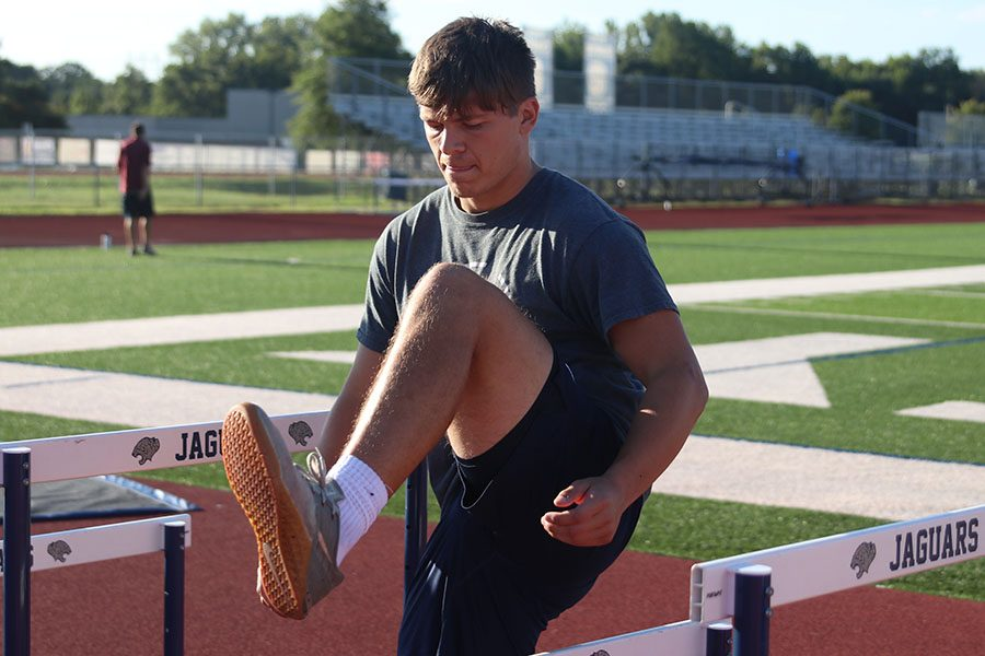 Lifting his leg over the hurdle, senior Carson Caldwell works out on the track due to the construction making the old weight room inaccessible.
