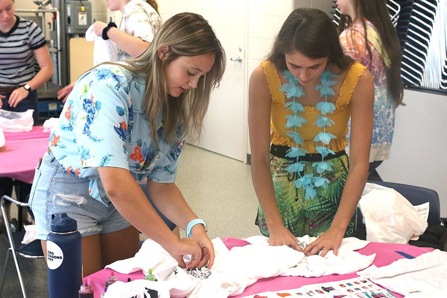 Twisting their T-shirts, seniors Audrey Grabmeir and Abby Miller started the first part in the process of making a tie-dye T-shirt.