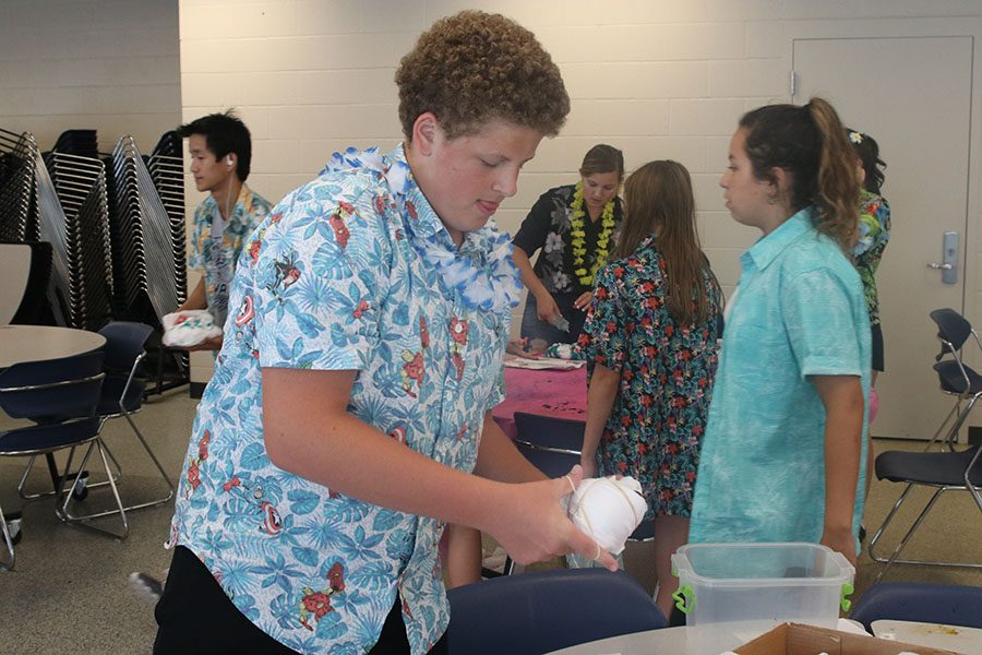Placing rubber bands around his shirt, sophomore Declan Taylor prepares to dye his shirt.