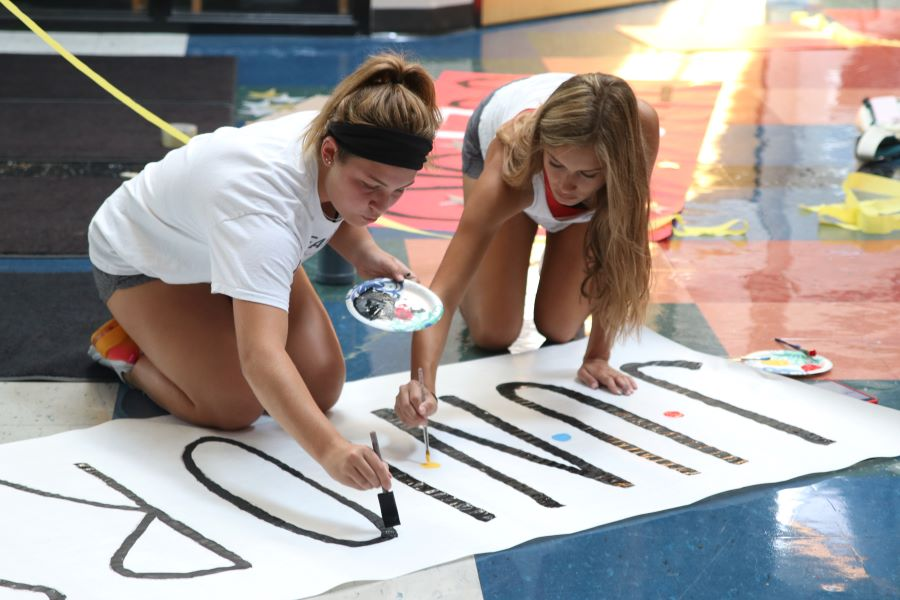 Juniors Grace Moser and Avery Rutkowski paint a sign to hang by the junior locker banks.