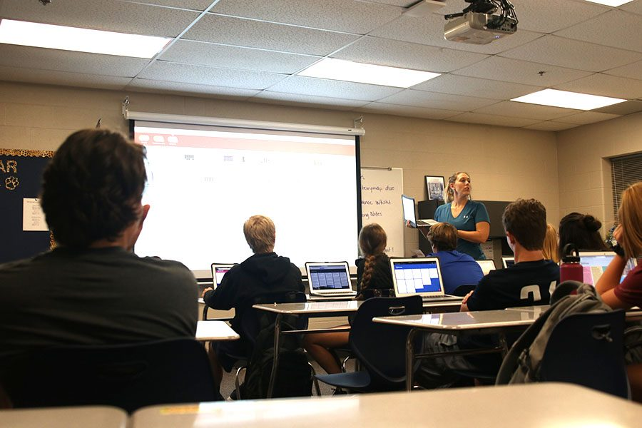 With Apple Classroom projected on the board, health teacher Sarah Haub stands in the front of the classroom teaching.
