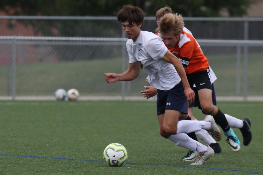 Junior Cael Denny, sticks his tongue out trying to dribble towards the goal.