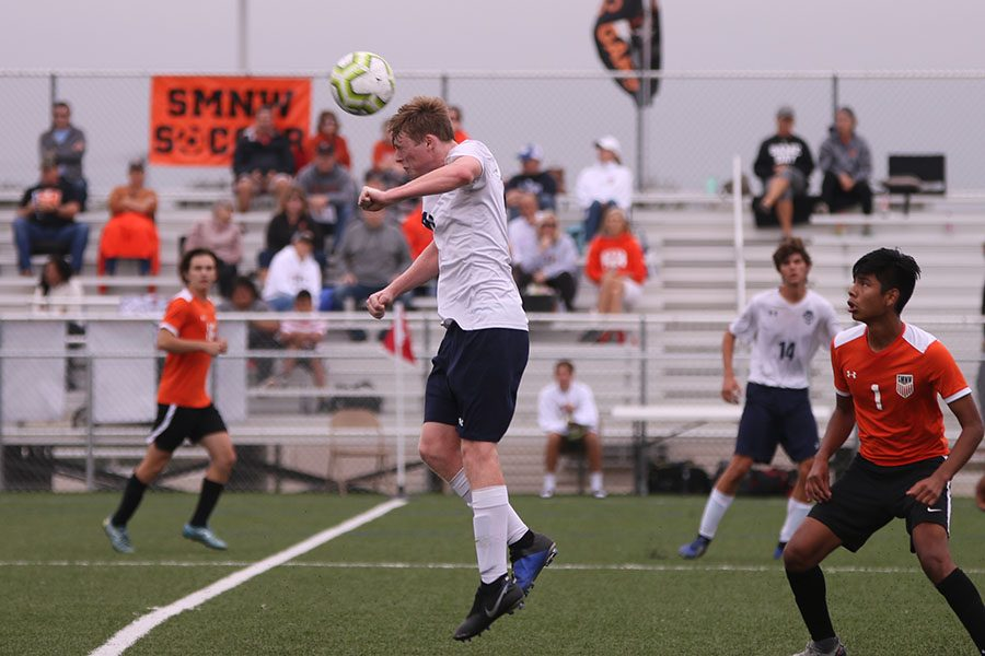 After the ball is punted down the field by the opposing keeper, senior Will Coacher jumps up to the receive the ball with his head. The game ended in a 2-2 tie Saturday, Sept. 28.