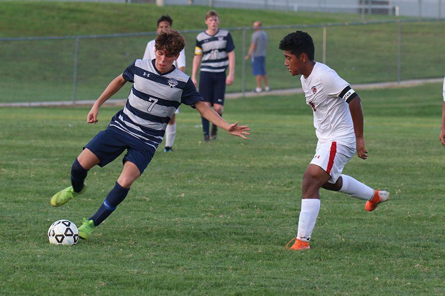 Sophomore Yahel Anderson skillfully maneuvers around Olathe North player.