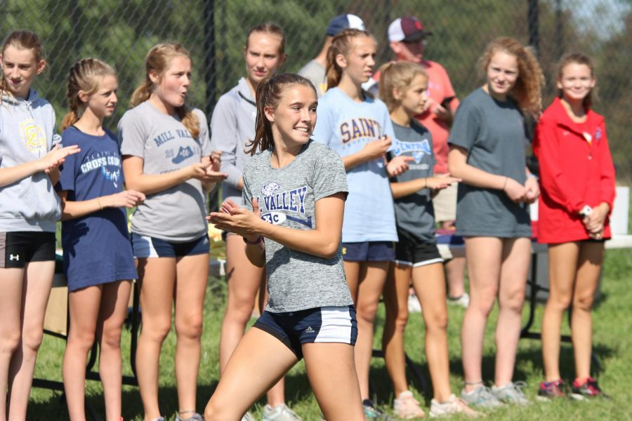 Going to receive her medal, senior Molly Haymaker cheers on her teammates.