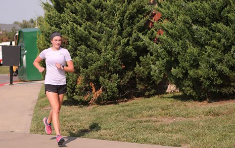 Less than two months after her open-heart surgery, sophomore Logan Pfeister finishes her run at cross country practice.