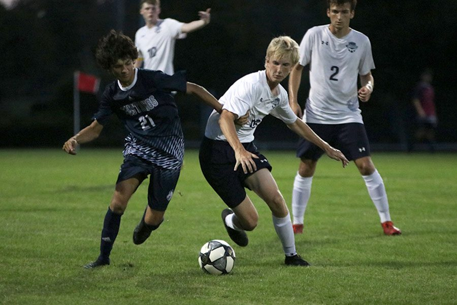 Attempting to block his opponent, sophomore Sutton Sick tries to steal the ball.