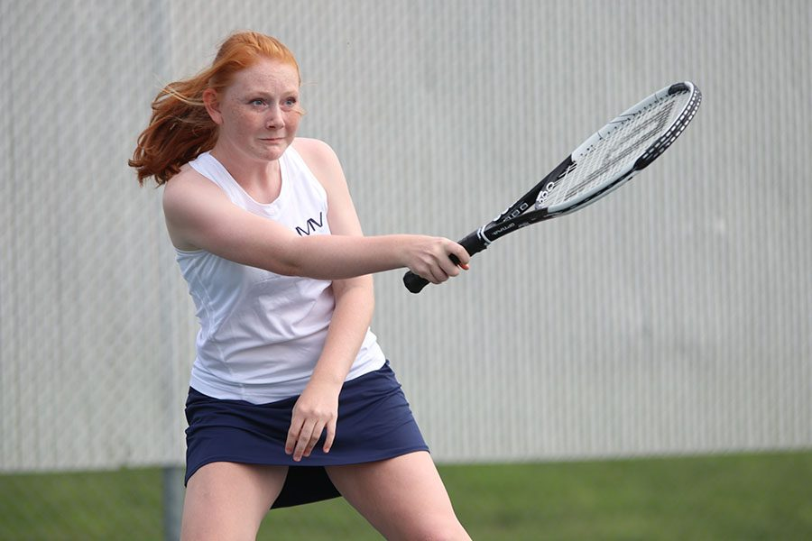 Following through on a forehand hit, sophomore Lauren Butler returns the ball to her opponent. She and teammate Carli Dupriest won this match against Olathe Northwest on Wednesday, September 4.