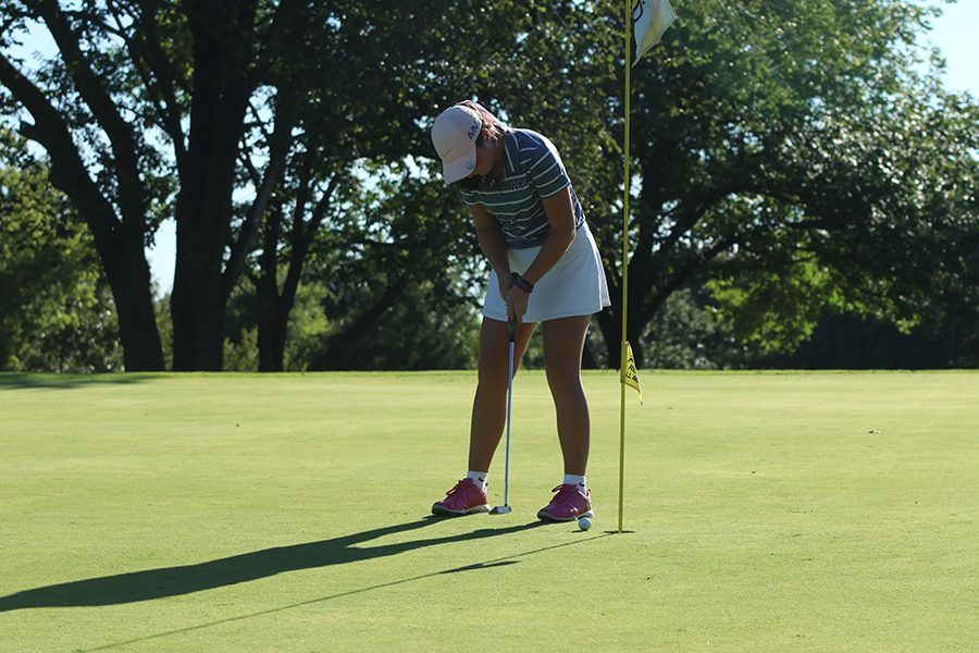 Putter in hand, sophomore Libby Green putts the ball.