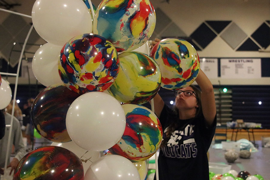 Junior Katherine Weigel ties balloons together to create a balloon arch.