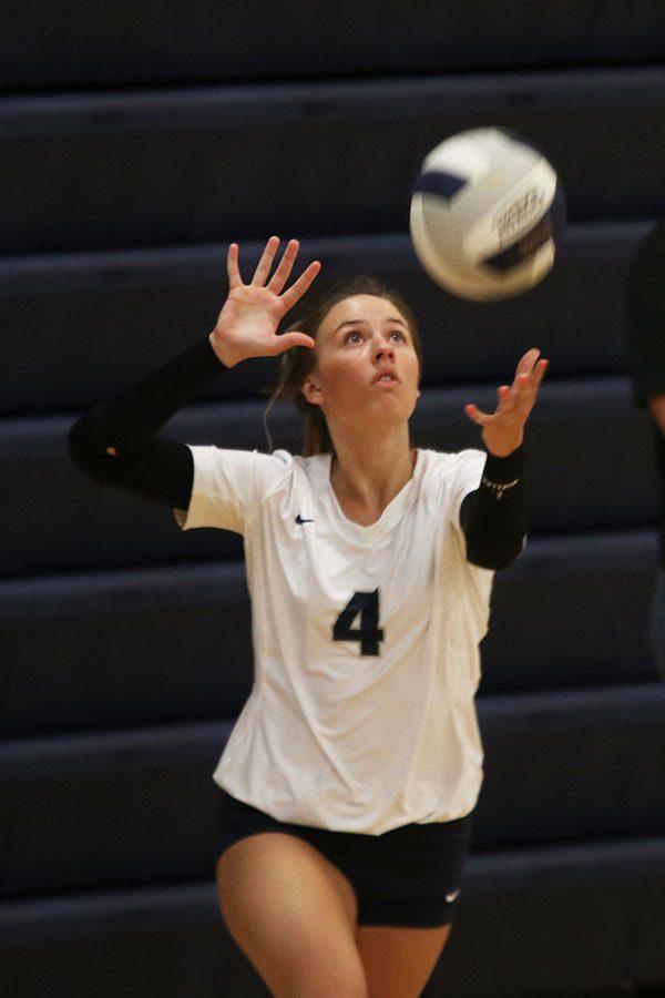 Eyes locked on the ball, senior Emma Fox serves.
